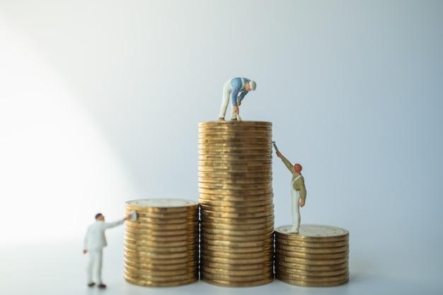 Bedrijfs-, geld- en spaarconcept. groep mensen die van het arbeiders de miniatuurcijfer en stapel gouden muntstukken schoonmaken schilderen.