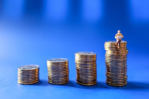 Bedrijfs-, geldinvesteringen- en planningsconcept. mensen van het zakenman miniatuurcijfer stellen zittend en leesboek op stapel gouden muntstukken op blauwe achtergrond voor.