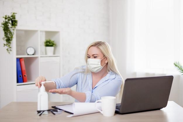 Bedrijfs-, gezondheidszorg-, veiligheids- en coronavirus pandemisch concept - jonge vrouw met masker die met laptop werkt en ontsmettingsmiddel thuis of op kantoor gebruikt