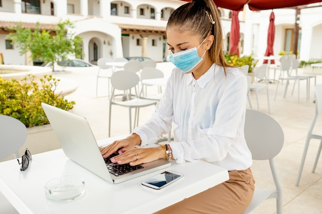 Bedrijfs jonge vrouw buiten met laptop op bartafel die beschermend masker tegen coronavirus pandemie draagt. nieuwe normale freelance job activiteit zelfstandig ondernemer overal werkzaam met mobiel internet