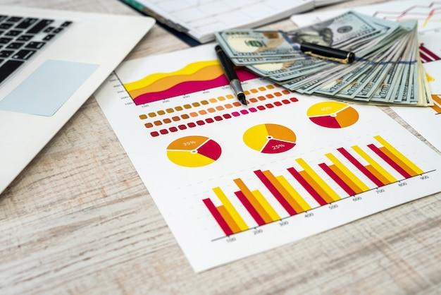 Bedrijfs-, kantoor- en geldconcept - grafiek of grafiek papier ons geld op tafel
