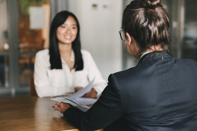 Bedrijfs-, loopbaan- en plaatsingsconcept - foto van achterkant van zakenvrouw interviewen en praten met vrouwelijke sollicitant tijdens sollicitatiegesprek
