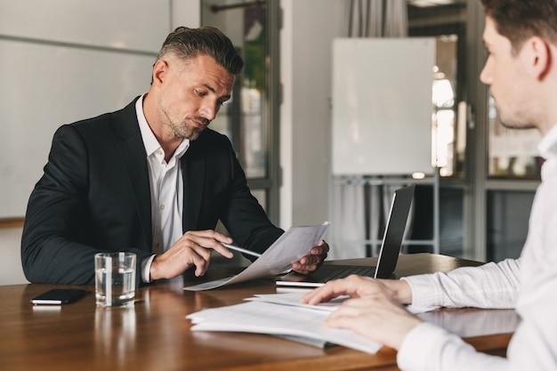 Bedrijfs-, loopbaan- en plaatsingsconcept - kaukasische zakenman 30s die met mannelijke werkgever onderhandelen en zijn cv lezen tijdens sollicitatiegesprek op kantoor