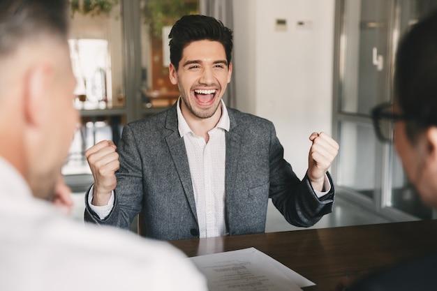 Bedrijfs-, loopbaan- en plaatsingsconcept - succesvolle blanke man 30s vreugde en gebalde vuisten tijdens sollicitatiegesprek op kantoor, met werknemers van groot bedrijf