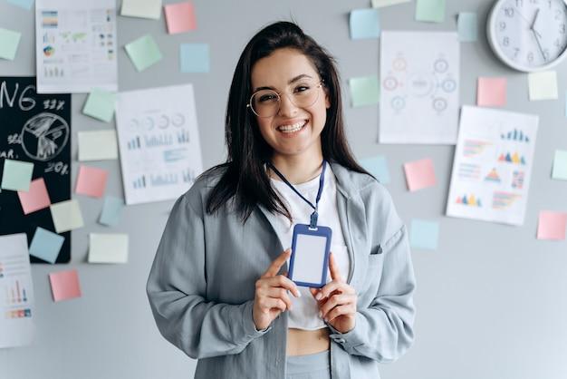 Bedrijfs meisje dat naamplaatje in het bureau toont