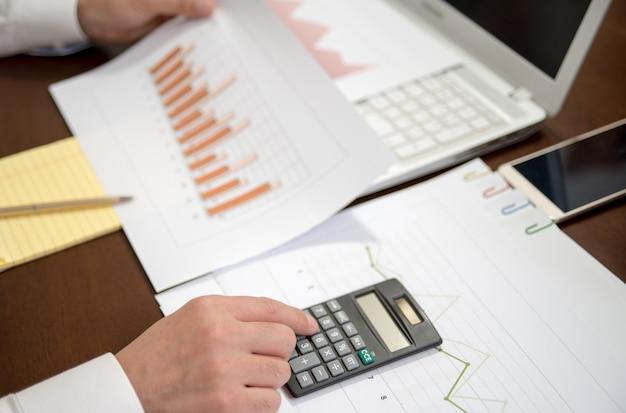 Bedrijfs mens controleert met een calculator.