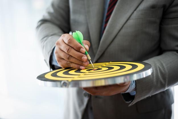 Bedrijfs mens die aan centrum van dartboard voor aspiratieconcept poiting.
