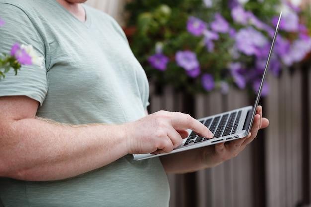 Bedrijfs mens die aan een laptop zitting op de straat werkt