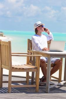 Bedrijfs mens die door celtelefoon roept op wit strand