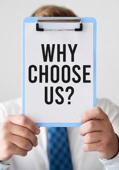 Bedrijfs mens die een klembord met waarom voor ons kiest vraag houdt