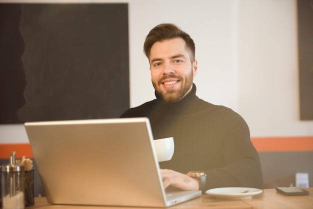 Bedrijfs mens die een koffie in een koffiewinkel heeft en aan zijn laptop werkt.