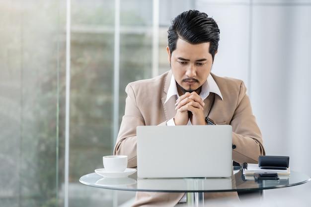Bedrijfs mens die en met laptop computer denkt werkt
