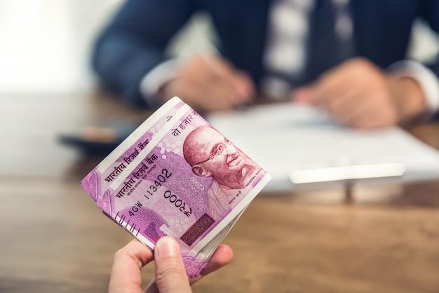 Bedrijfs mens die geld geeft in de vorm van indische roepies