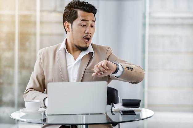 Bedrijfs mens die horloge kijkt en met de tijd wordt geschokt