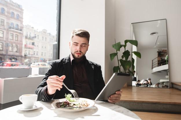 Bedrijfs mens die in een restaurant dineert en een tablet gebruikt.