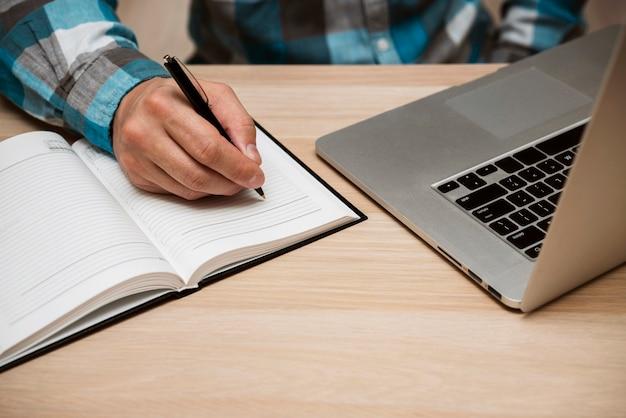 Bedrijfs mens die in leeg notitieboekje schrijft