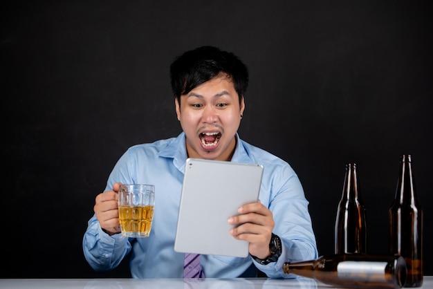 Bedrijfs mens die laptop met een biermok houdt
