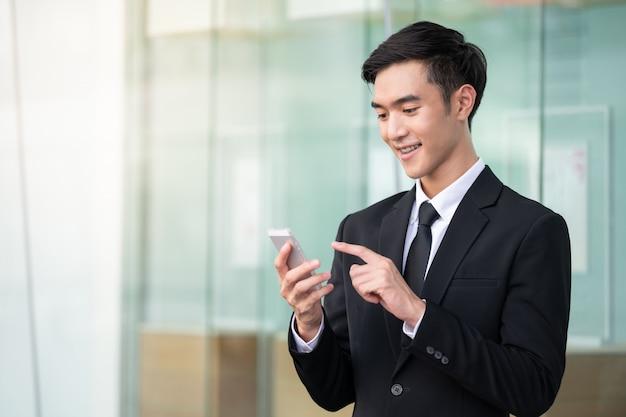 Bedrijfs mens die mobiele telefoon voor het werk met behulp van of online winkelt.