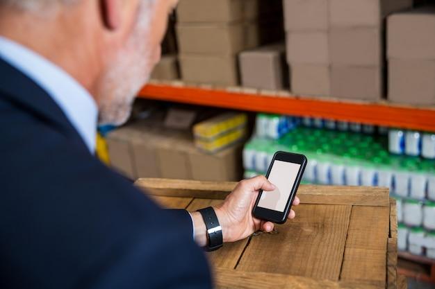 Bedrijfs mens die zijn smartphone gebruikt