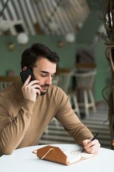 Bedrijfs mens met agenda die over telefoon spreekt