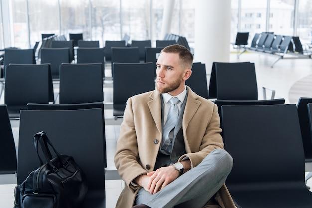 Bedrijfs mens met koffer in zaal van luchthaven