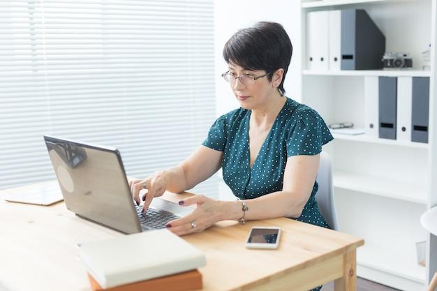 Bedrijfs-, mensen- en technologieconcept - vrouw van middelbare leeftijd met laptop die thuis werkt of