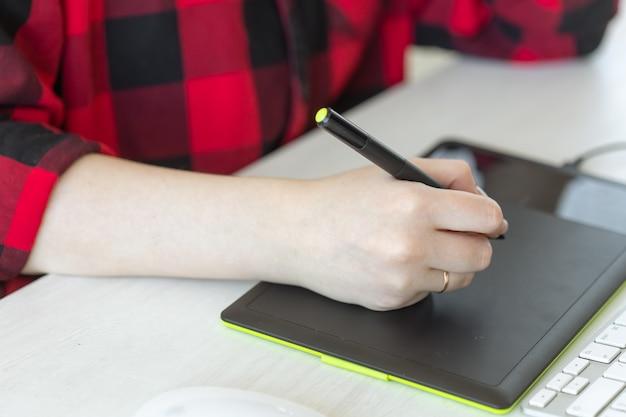 Bedrijfs-, ontwerper- en animatorconcept - close-up van de hand van grafisch ontwerperstekening op de tablet