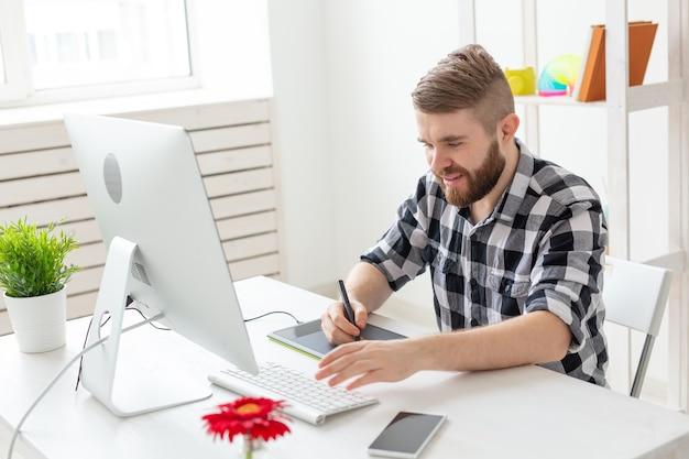 Bedrijfs-, ontwerper- en animatorconcept - knappe manillustrator of kunstenaar trekt op de grafische tablet.