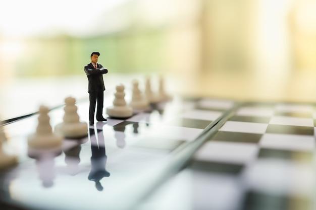 Bedrijfs, teamwork en strategie planningsconcept. sluit omhoog van cijfer van zakenman het miniatuurmensen status op schaakbord tussen pandschaakstukken en exemplaarruimte.