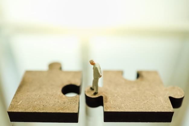 Bedrijfs-, teamwork-, planning- en werkconcept. sluit omhoog van mensen van het zakenman de miniatuurcijfer die en zich tussen twee houten figuurzaagstuk met exemplaarruimte bevinden te kijken te scheuren.