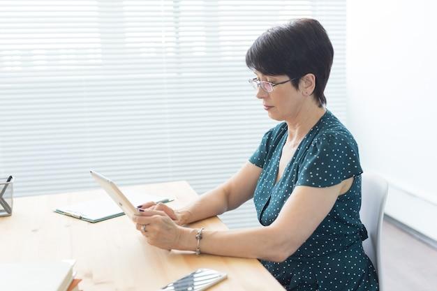 Bedrijfs-, technologie- en mensenconcept - een serieuze vrouw die in bureau zit en een tablet gebruikt
