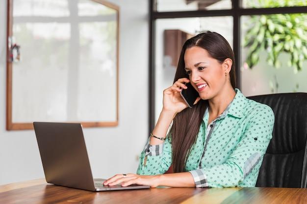 Bedrijfs vrouw die bij de telefoon en het glimlachen spreekt