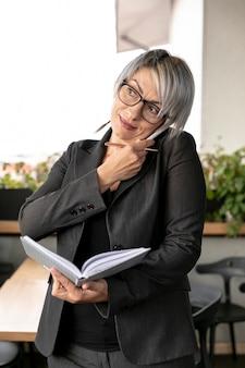 Bedrijfs vrouw die bij telefoon en het schrijven spreekt