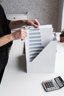 Bedrijfs vrouw die bureaudossiers schikt