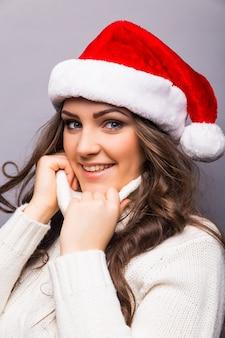 Bedrijfs vrouw die de rode hoed van de kerstman draagt. glimlachend santameisje geïsoleerd portret.