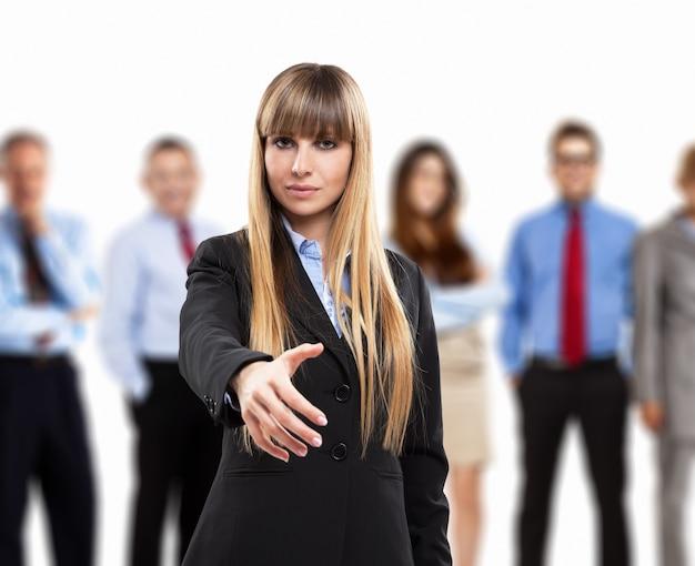 Bedrijfs vrouw die een handdruk aanbiedt. groep mensen op de achtergrond