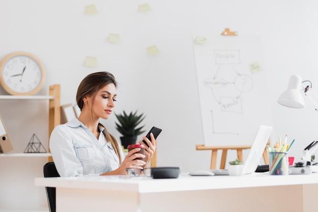 Bedrijfs vrouw die een kop van koffie houdt en op telefoon kijkt