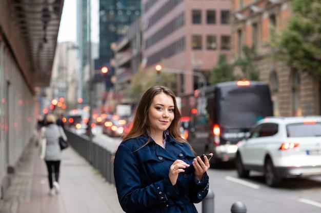 Bedrijfs vrouw die een plaats in de telefoon, voor een commerciële vergadering kijkt.