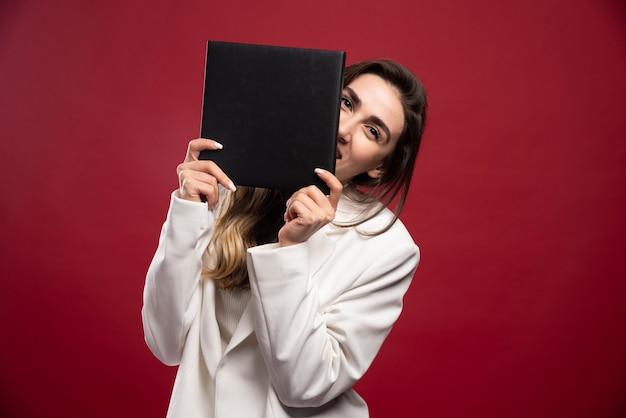 Bedrijfs vrouw die haar gezicht behandelt met een notitieboekje