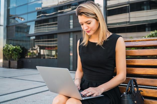 Bedrijfs vrouw die haar laptop in openlucht met behulp van.