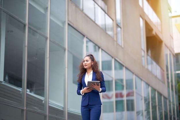 Bedrijfs vrouw die in de straat loopt