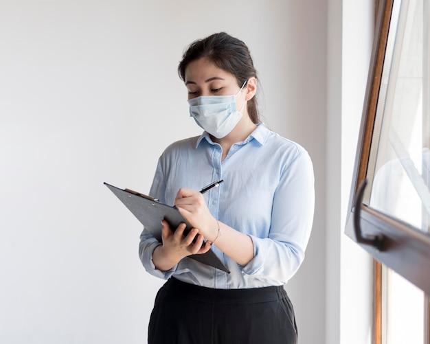 Bedrijfs vrouw die medisch masker draagt