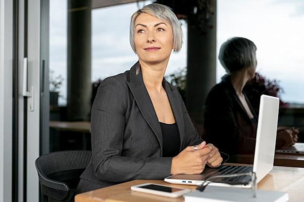 Bedrijfs vrouw die met laptop weg kijkt