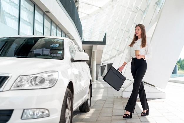 Bedrijfs vrouw die naar de auto gaat
