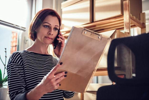 Bedrijfs vrouw die op de telefoon op het kantoor spreekt