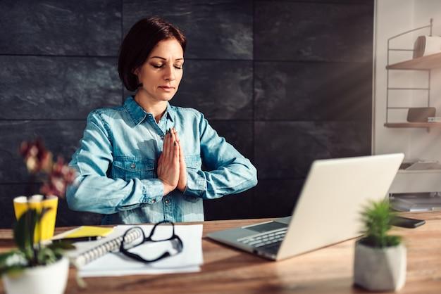 Bedrijfs vrouw die op het werk mediteert