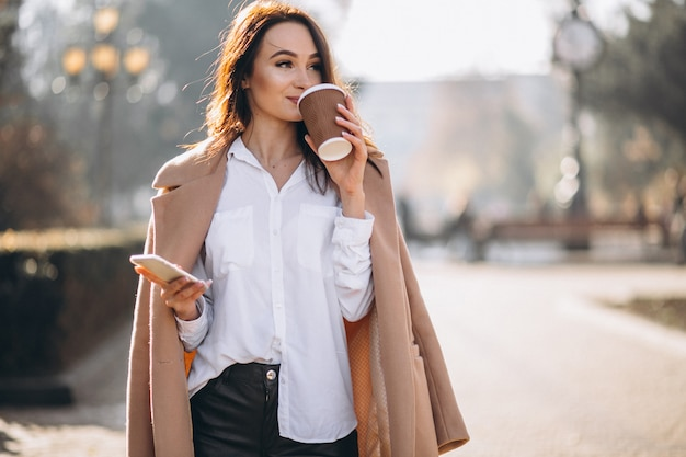 Bedrijfs vrouw die op telefoon en het drinken koffie spreekt