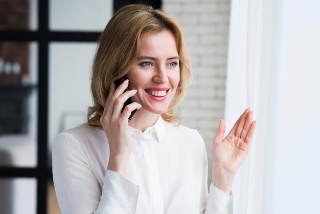 Bedrijfs vrouw die op telefoon en het glimlachen spreekt