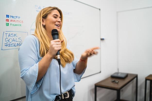 Bedrijfs vrouw die werkplan in conferentie verklaart.