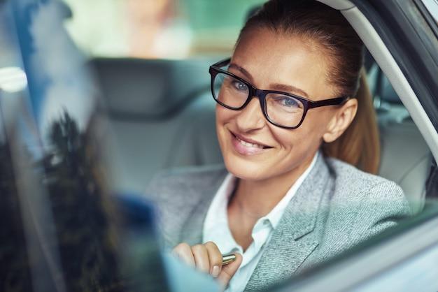 Bedrijfs vrouw in auto. vrolijke dame van middelbare leeftijd dragen bril zittend op de achterbank in de taxi, camera kijken en glimlachen, transport en voertuig concept, mensen uit het bedrijfsleven in taxi